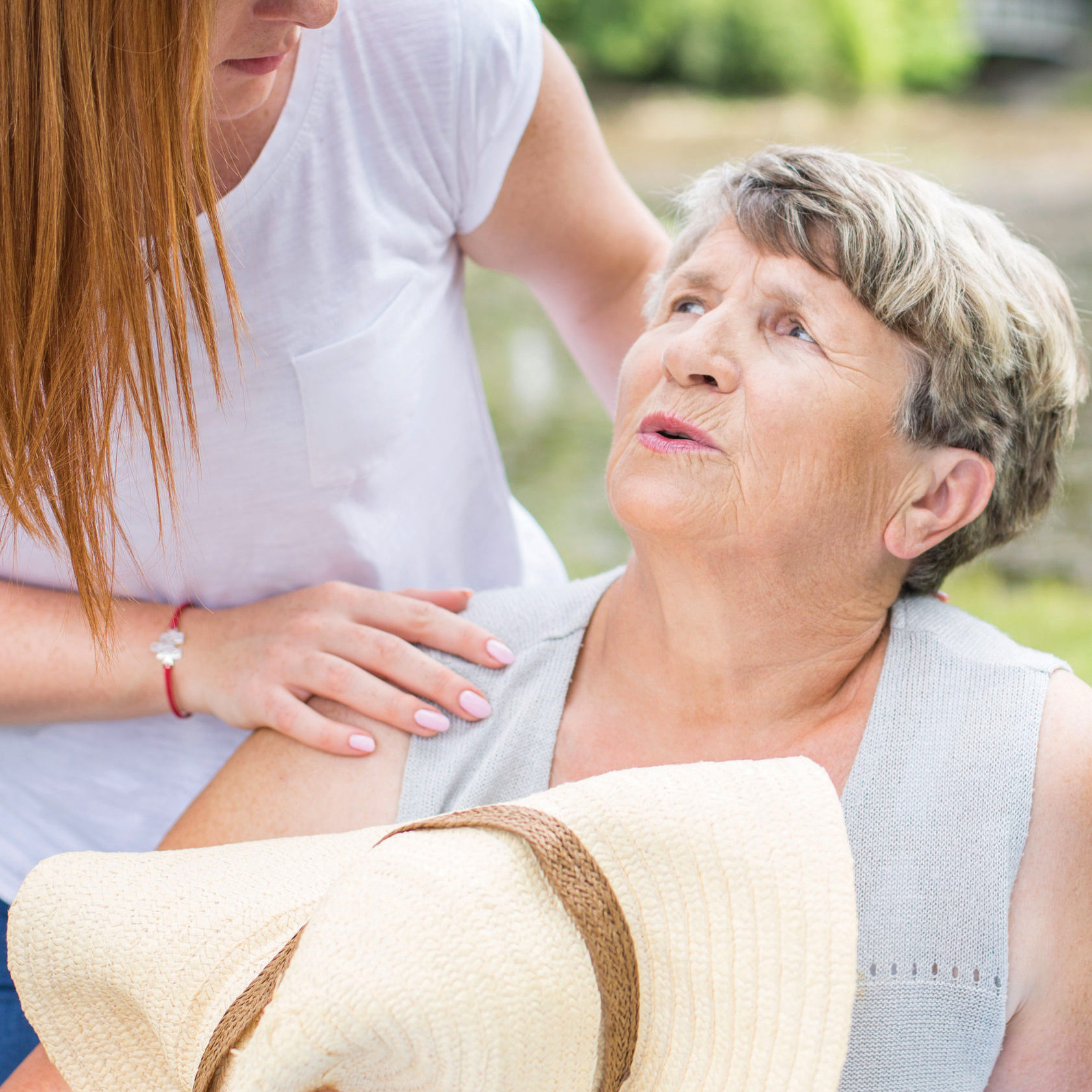 56279401 - shot of an elderly lady holding a sun hat, feeling faint, and a young woman assisting her